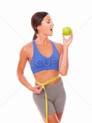 Latin young woman biting apple to lose weight