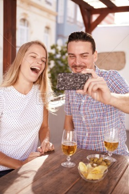 Laughing couple taking a happy selfie
