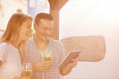 Laughing couple with beers and touchpad