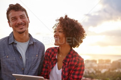 Laughing young couple holding a tablet