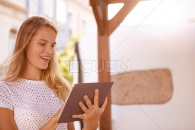 Lovely blond smiling widely with touchpad