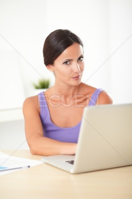 Lovely hispanic woman looking displeased at work