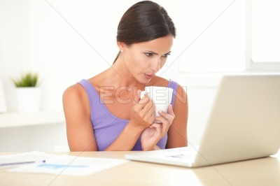 Lovely lady holding a coffee mug while working