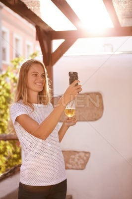 Lovely smiling blond girl taking a selfie