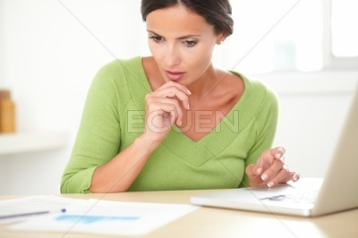 Lovely woman wondering while working on laptop