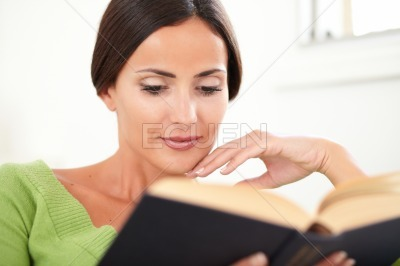 Peaceful woman reading a book at indoors