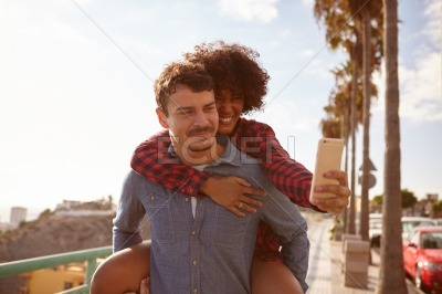 Piggy back couple taking a selfie