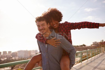 Playful young couple playing piggy back