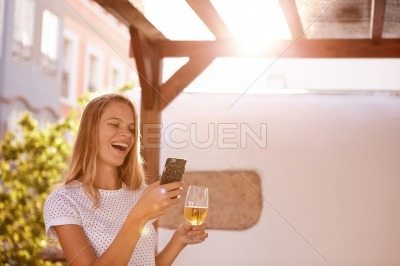 Pretty blond girl with beer and cellphone
