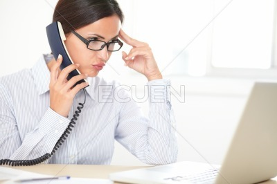 Pretty female executive conversing on the phone