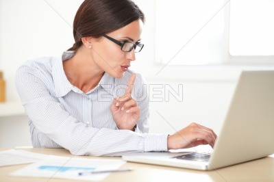 Pretty female executive using her laptop