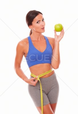 Pretty woman in sport clothing dieting on fruit