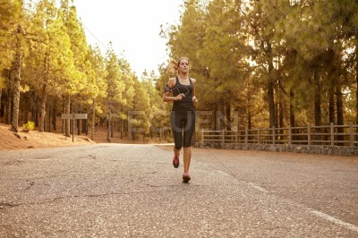 Pretty young brunette jogging through forest
