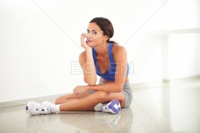 Pretty young female sitting in yoga class