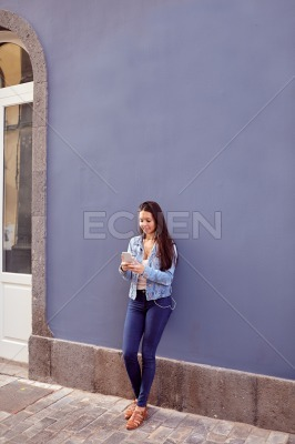 Pretty young girl leaning against a blue wall