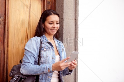 Pretty young girl looking at cellphone curiously