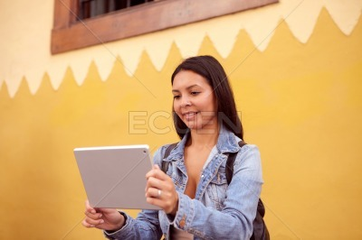 Pretty young girl reading on tablet pc