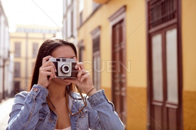 Pretty young girl taking a picture in an alley