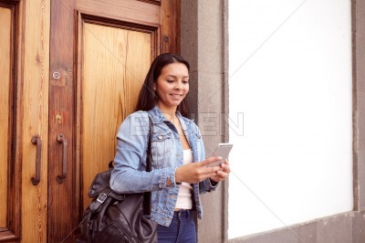 Pretty young girl with a backpack reading message
