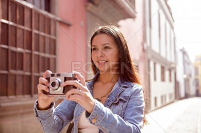 Pretty young girl with a camera looking ahead
