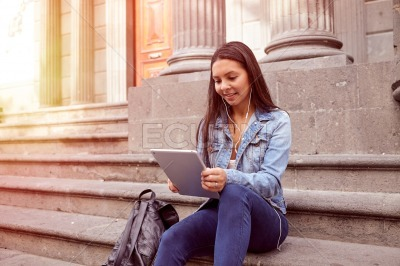 Pretty young girl with backpack looking at tablet