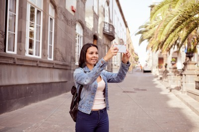 Pretty young girl with cell phone and backpack