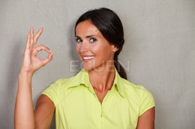 Satisfied woman showing ok sign and smiling