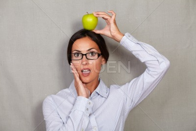 Shocked well-dressed female with apple on head