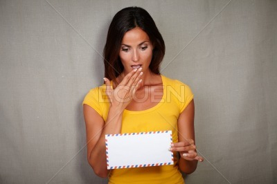 Shocked woman holding letter while standing