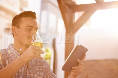 Short haired man with beer and touchpad