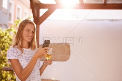 Smiling blond woman with cellphone and beer