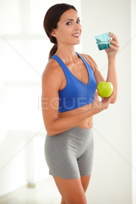 Smiling fit woman holding apple and glass of water
