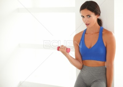 Sporty hispanic woman training with a dumbbell