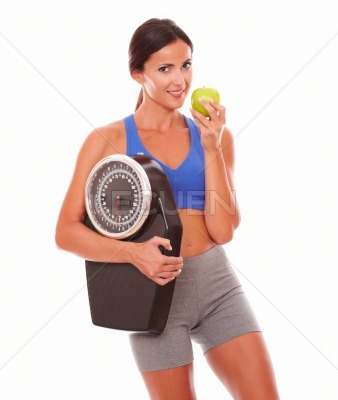 Sporty young woman eating apple for weight loss