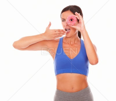 Sporty young woman holding cake on face
