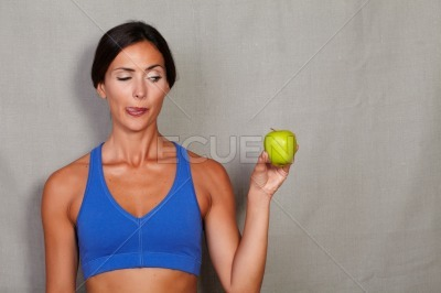 Standing woman licking his lip and showing apple