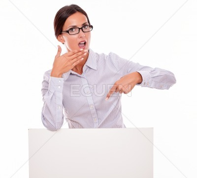 Surprised brunette woman with blank placard