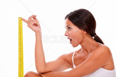 Surprised brunette woman with tape measure