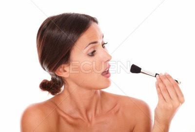 Surprised latin female looking at make up brush