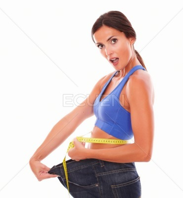 Surprised sporty woman measuring her waist