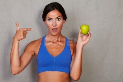 Surprised woman pointing to apple with open mouth