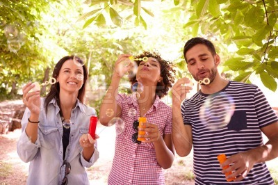 Three friends having fun with bubbles