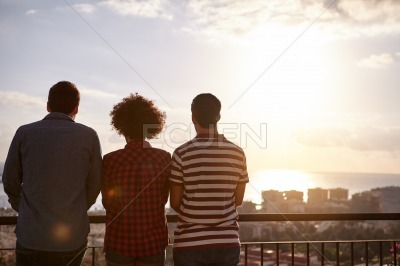 Three friends looking at a sunset