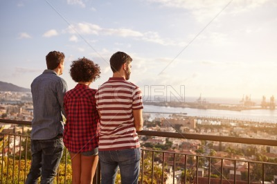 Three friends looking out over the cityscape