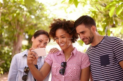 Three happy people smiling at cellphone