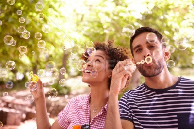 Two happy young friends blowing bubbles