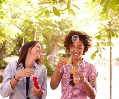 Two laughing young girls blowing bubbles