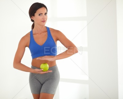 Woman in sports clothing holding apple