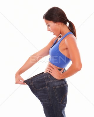 Woman with healthy lifestyle pulling jeans