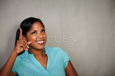 Young african woman pointing up while smiling
